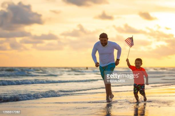 running with an american flag on the beach - sarasota stock pictures, royalty-free photos & images