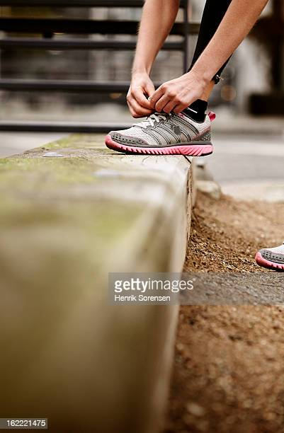 Running, woman ties her shoes