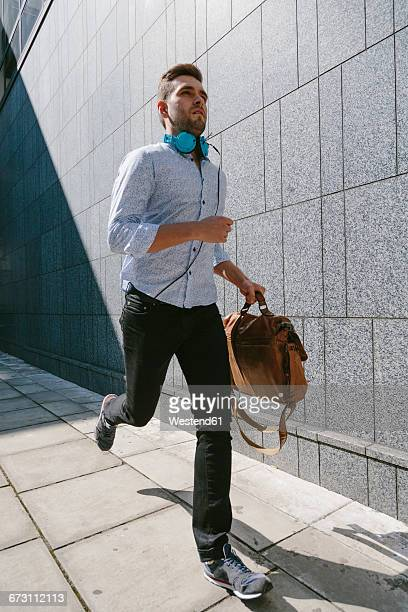 Running young businessman with headphones and leather bag