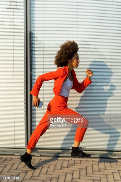 running young woman with smartphone wearing fashionable red pantsuit - vertical stock pictures, royalty-free photos & images