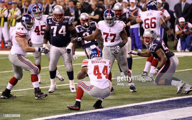 Runningback Ahmad Bradshaw of the New York Giants runs the ball for a 6 yard touchdown in the fourth quarter against the New England Patriots during...