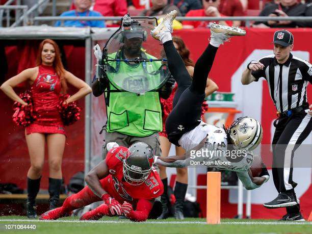Runningback Alvin Kamara of the New Orleans Saints is flipped by Linebacker Adarius Taylor of the Tampa Bay Buccaneers during the game at Raymond...