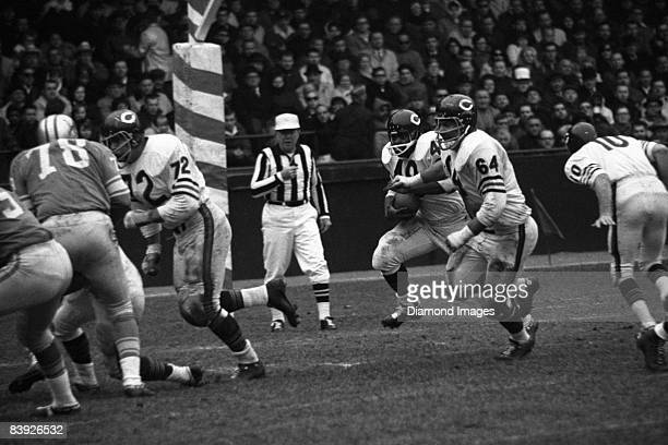 Runningback Andy Livingston of the Chicago Bears runs with the ball as tackle Jim Cadile and guard Mike Rabold block for Livingston during a game on...