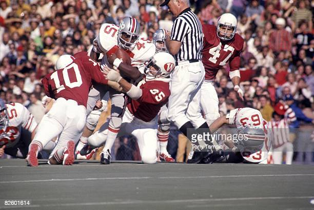 Runningback Archie Griffin of the Ohio States Buckeyes runs with the ball and tries to break a tackle by two defenders for the Wisconsin Badgers...