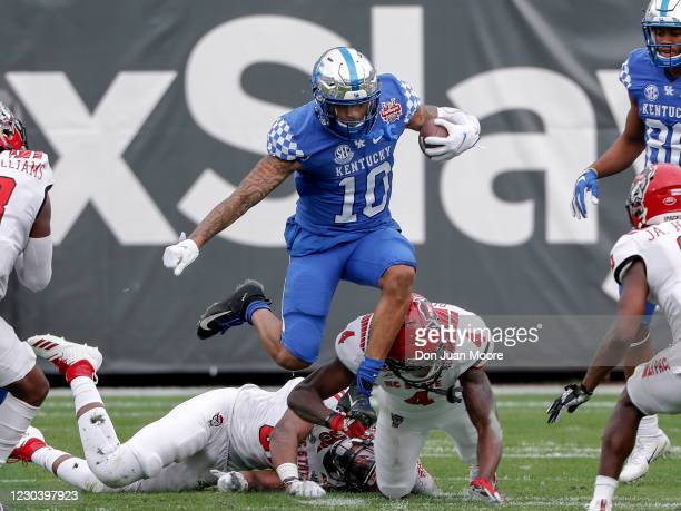 Runningback Asim Rose of the University of Kentucky Wildcats leaps over Defensive Back Cecil Powell of the North Carolina State Wolfpack on a running...