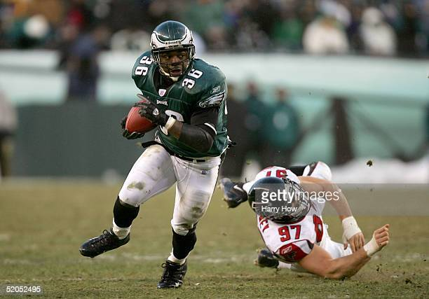 Runningback Brian Westbrook of the Philadelphia Eagles breaks through a tackle attempt by Patrick Kerney of the Atlanta Falcons in the third quarter...