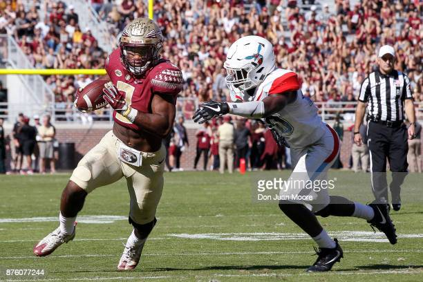 Runningback Cam Akers of the Florida State Seminoles avoids a tackle by Cornerback Keyjuan Selby of the Delaware State Hornets during the game at...