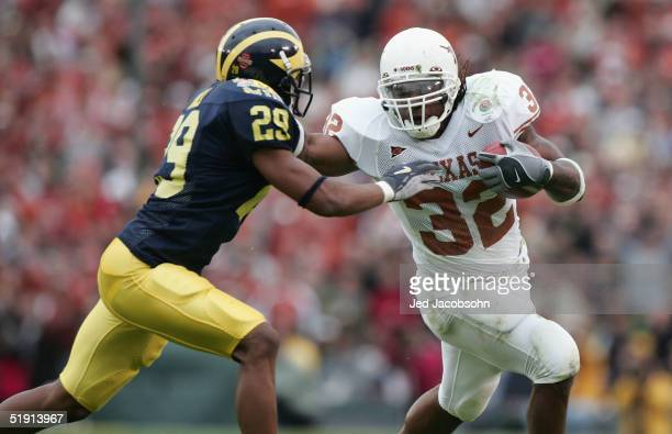 Runningback Cedric Benson of the Texas Longhorns runs with the ball underpressure from Leon Hall of the Michigan Wolverines in the 91st Rose Bowl...