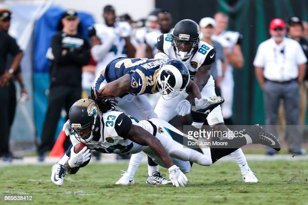Runningback Chris Ivory of the Jacksonville Jaguars dives for extra yard over Cornerback Trumaine Johnson of the Los Angeles Rams during the game at...
