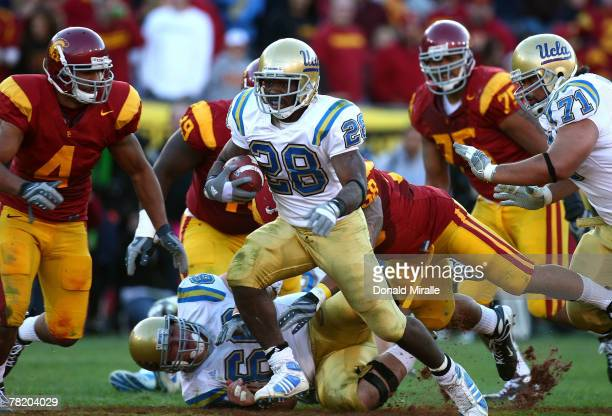 Runningback Chris Markey of the UCLA Bruins carries the ball under pressure from Kevin Ellison of the USC Trojans during the third quarter of the...