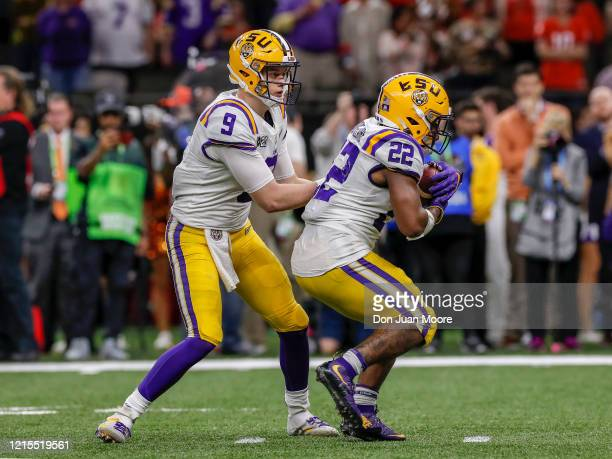 Runningback Clyde EdwardsHelarie takes a hand off from Quarterback Joe Burrow of the LSU Tigers during the College Football Playoff National...