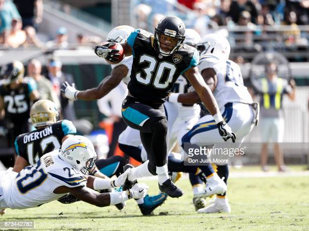 Runningback Corey Grant of the Jacksonville Jaguars avoids a tackle by Cornerback Desmond King of the Los Angeles Chargers on a fake punt return for...
