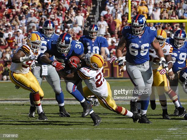 Runningback Derrick Ward of the New York Giants tries to break the tackle of safety Sean Taylor of the Washington Redskins during a game on September...