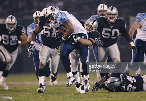Runningback Eddie George of the Tennessee Titans holds tight while tackled by safety Rod Woodsen of the Oakland Raiders during the AFC Championship...