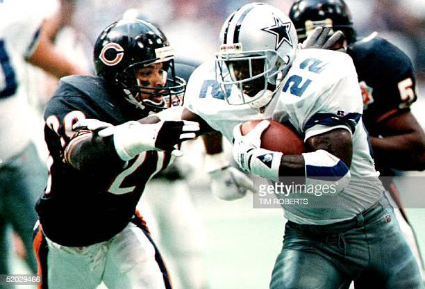 Runningback Emmitt Smith of the Dallas Cowboys runs past free safety Mark Carrier of the Chicago Bears 27 December 1992 in Texas on his way to a...
