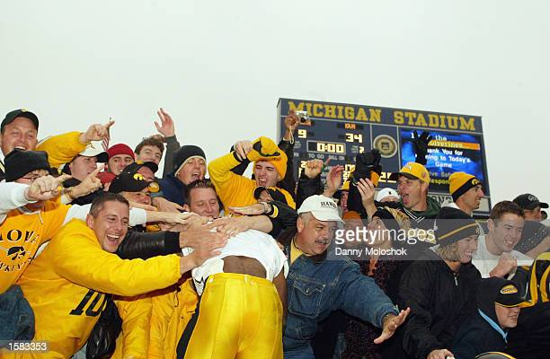 Runningback Fred Russell of the Iowa Hawkeyes jumps into the stands full of Hawkeye faithful after his team defeated the Michigan Wolverines 34-9 at...