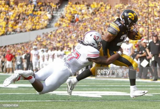 Runningback Ivory Kelly-Martin of the Iowa Hawkeyes runs up the field for a touchdown during the second half against linebacker Kyle Pugh of the...