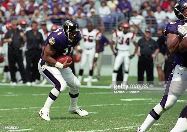 Runningback Jamal Lewis of the Baltimore Ravens carries the ball for a few extra yards after receiving a handoff from Quarterback Tony Banks during a...