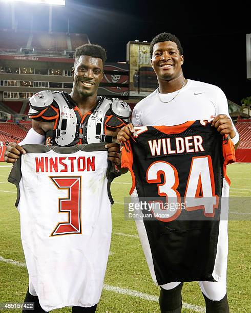 Runningback James Wilder Jr #32 of the Cincinnati Bengals and Quarterback Jameis Winston of the Tampa Bay Buccaneers pose for a photo with each...