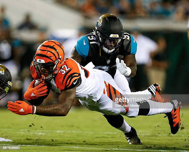 Runningback Jeremy Hill of the Cincinnati Bengals dives for extra yards while avoiding a tackle by defensive end Yannick Ngakoue of the Jacksonville...