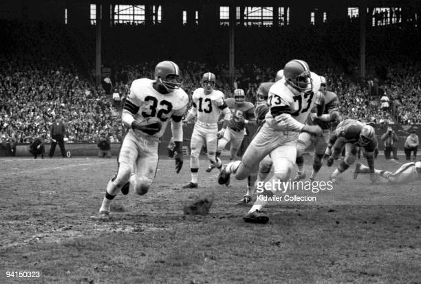 Runningback Jim Brown of the Cleveland Browns runs on a sweep behind tackle Monte Clark as quarterback Frank Ryan watches from the back of the play...