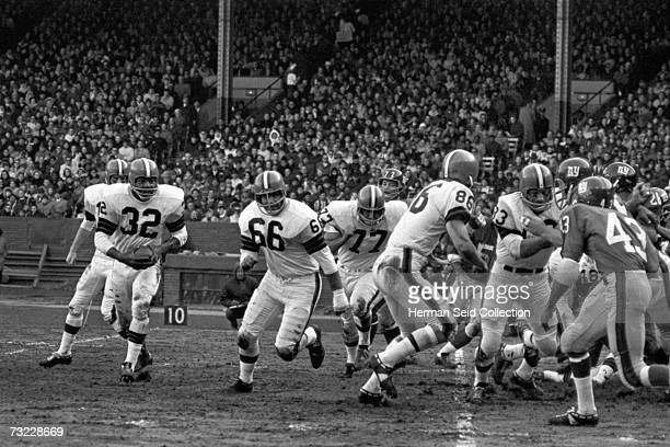Runningback Jim Brown of the Cleveland Browns runs the sweep after receiving the ball from quarterback Frank Ryan during a game on October 24 1965...