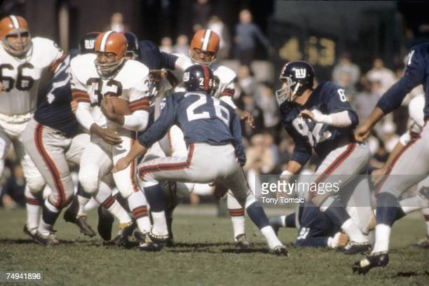 Runningback Jim Brown of the Cleveland Browns runs with the ball during a game on October 25 1964 against the New York Giants at Municipal Stadium in...