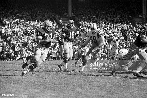 Runningback Jim Taylor of the Green Bay Packers runs the ball as Gino Marchetti of the Baltimore Colts tries to run him down during a game on October...