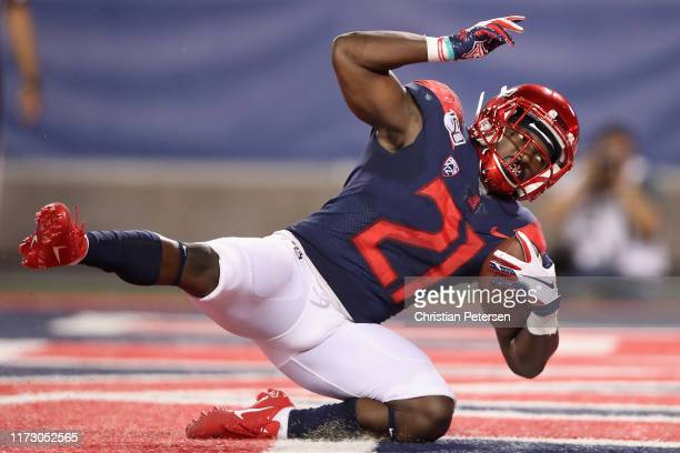 Runningback JJ Taylor of the Arizona Wildcats scores on a 25 yard rushing touchdown against the Northern Arizona Lumberjacks during the first half of...