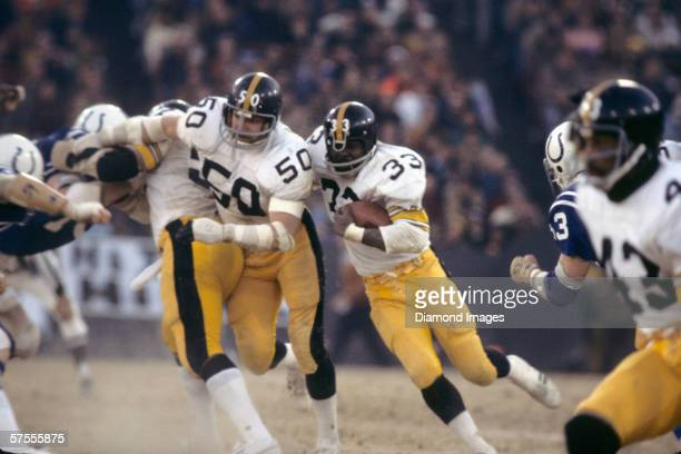 Runningback John 'Frenchy' Fuqua of the Pittsburgh Steelers looks for running room behind the blocking of Jim Clack during the AFC Divisional Playoff...