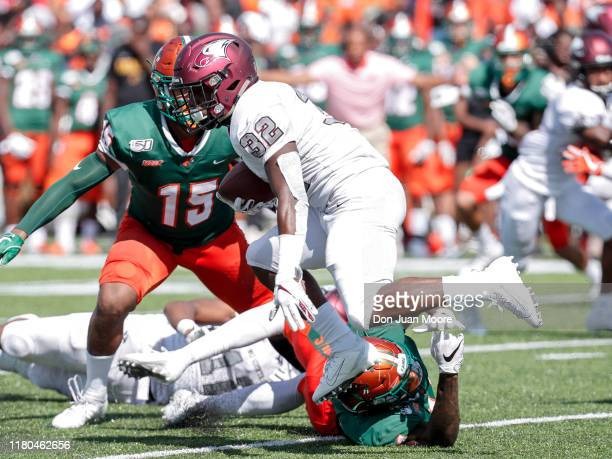 Runningback Jordan Freeman of the North Carolina Central Eagles avoids a tackle by Defensive End Isaiah Land and Linebacker Elijah Richardson of the...