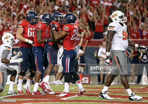 Runningback Ka'Deem Carey of the Arizona Wildcats celebrates with Austin Hill after Carey scored on a 13 touchdown reception against the Oklahoma...