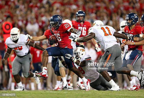 Runningback Ka'Deem Carey of the Arizona Wildcats rushes the football for a 25 yard touchdown past Daytawion Lowe and Shaun Lewis of the Oklahoma...