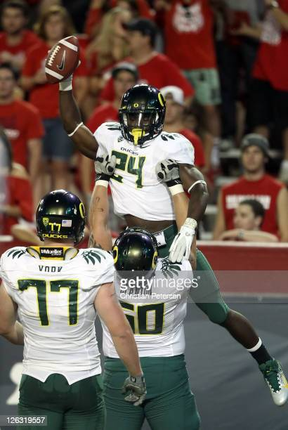 Runningback Kenjon Barner of the Oregon Ducks is hoisted up by Ryan Clanton after scoring on a 6 yard rushing touchdown against the Arizona Wildcats...