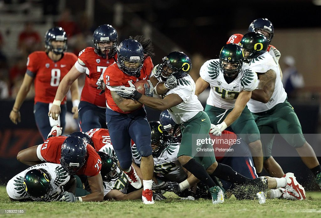 Runningback Keola Antolin #2 of the Arizona Wildcats rushes the football against Eddie Pleasant #11 of the Oregon Ducks during the third quarter of the college football game at Arizona Stadium on September 24, 2011 in Tucson, Arizona. The Ducks defeated the Wildcats 56-31.