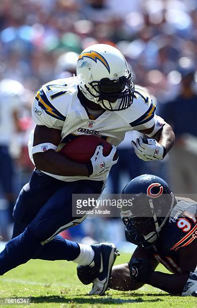 Runningback LaDainian Tomlinson of the San Diego Chargers runs against the tackle of Tommie Harris of the Chicago Bears during the 1st half of their...