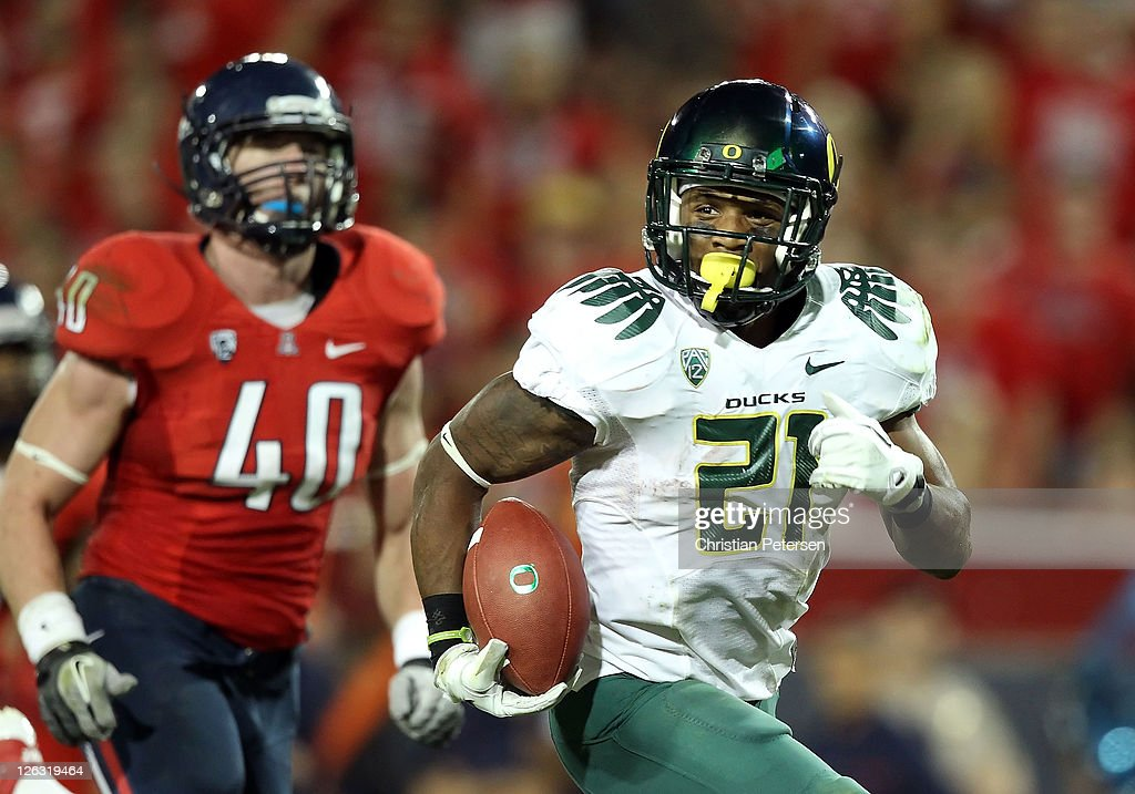 Runningback LaMichael James #21 of the Oregon Ducks carries the football on a 19 yard rushing touchdown past linebacker Derek Earls #40 of the Arizona Wildcats during the second quarter of the college football game at Arizona Stadium on September 24, 2011 in Tucson, Arizona.
