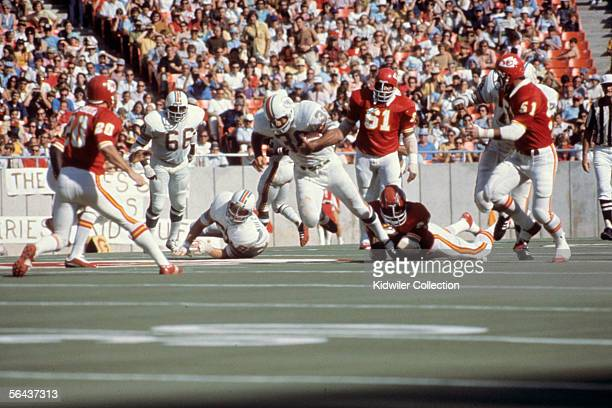 Runningback Larry Csonka of the Miami Dolphins tries to break the tackle of linebacker Willie Lanier of the Kansas City Chiefs during a game on...