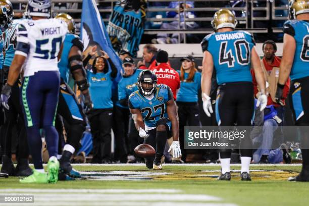 Runningback Leonard Fournette of the Jacksonville Jaguars uses his teammates as props for celebrating after a touchdown score during the game against...