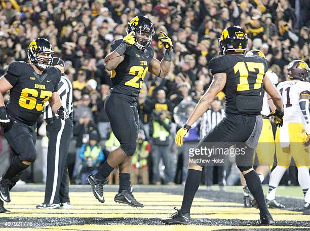 Runningback LeShun Daniels celebrates between offensive lineman Austin Blythe and wide receiver Jacob Hillyer of the Iowa Hawkeyes after a touchdown...