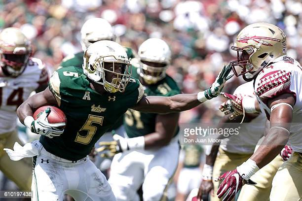Runningback Marlon Mack of the South Florida Bulls stiff arms Defensive End DeMarcus Walker of the Florida State Seminoles on a running play during...