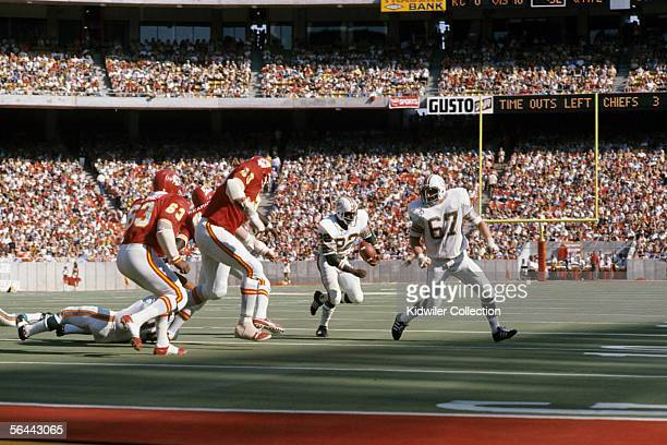 Runningback Mercury Morris of the Miami Dolphins looks for running room as Guard Bob Kuechenberg positions himself to block during a game against the...