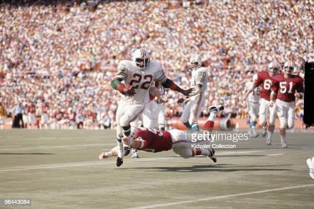 Runningback Mercury Morris of the Miami Dolphins steps out of the diving tackle attempt by linebacker Jim Cheyunski of the New England Patriots...