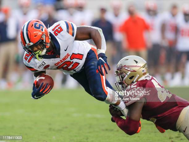 Runningback Moe Neal of the Syracuse Orange is tackled by Linebacker Jaleel McRae of the Florida State Seminoles during the game at Doak Campbell...