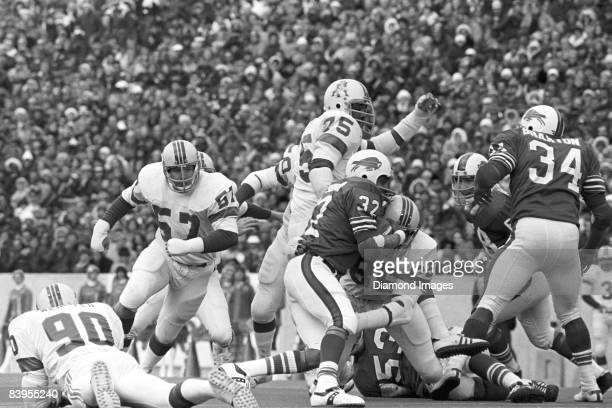 Runningback OJ Simpson of the Buffalo Bills tries to break the tackle of Julius Adams of the New England Patriots during a game on October 20 1974 at...