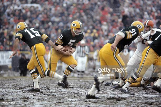 Runningback Paul Hornung of the Green Bay Packers receives the ball from quarterback Bart Starr as runningback Jim Taylor runs ahead to block for...