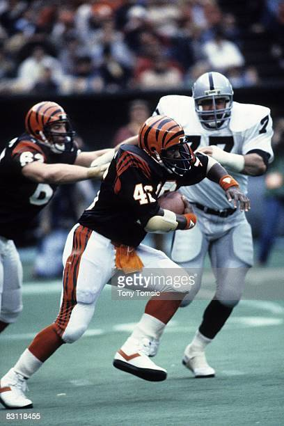 Runningback Pete Johnson of the Cincinnati Bengals runs with the ball as defensive lineman Lyle Alzado of the Los Angeles Raiders tries to tackle him...