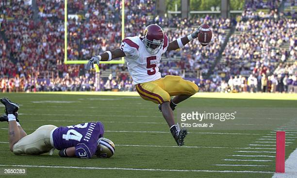 Runningback Reggie Bush of the University of Southern California Trojans scores a touchdown as he eludes Greg Carothers of the University of...