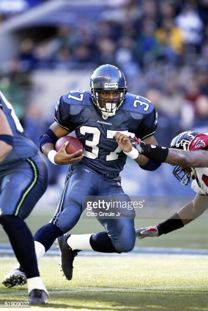Runningback Shaun Alexander of the Seattle Seahawks rushes against Bryan Scott of the Atlanta Falcons at Qwest Field on January 2 2005 in Seattle...