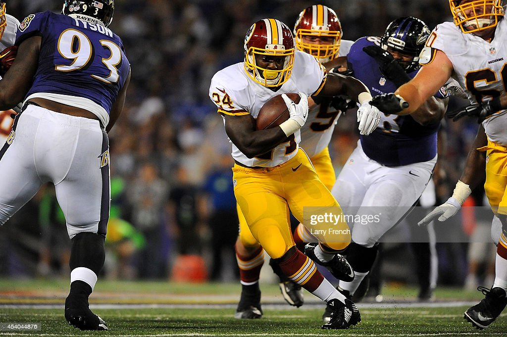 Runningback Silas Redd #24 of the Washington Redskins looks for a hole during a preseason game against the Baltimore Ravens at M&T Bank Stadium on August 23, 2014 in Baltimore, Maryland.